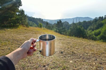 Cup with a hot tea over Beautiful view on mountain and field in summer