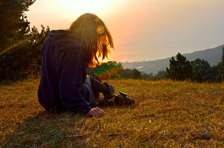 Girl siting on grass in the mountains over sun in her hair in summer