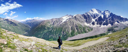 Tourist standing back over beautiful view on caucasian mountains and blue sky in summer. Nature of the Elbrus region.