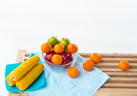 The fruit bowl with red apple,green apple and orange put beside dish of yellow corn,four oranges put on wooden timber board,healthy fruit,good for health and life