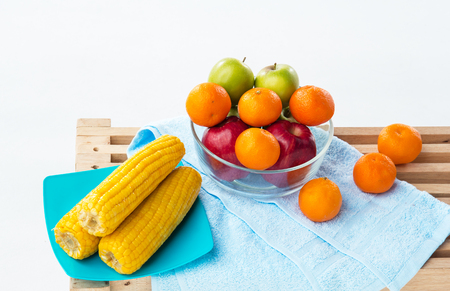 The fruit bowl with red apple,green apple and orange put beside dish of yellow corn,three oranges put beside glass bowl,on wooden timber board