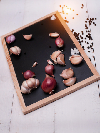 The shallot and garlic put on black board,warm light tone, blurry light around,the ingredient for cooking Banco de Imagens - 108295936