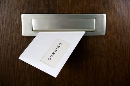 debt collection: A letter in a letterbox of a door, written DUNNING