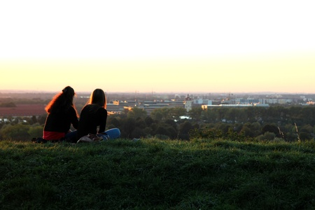 argumentative: Two girls sittion on a hill having good conversations