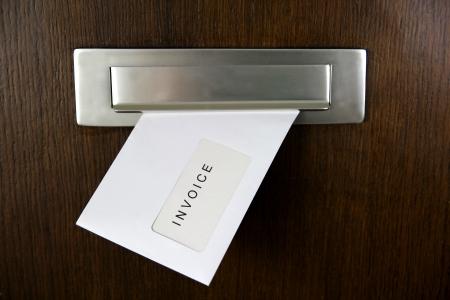schuld: Een brief in een brievenbus van een deur met schriftelijke FACTUUR Stockfoto