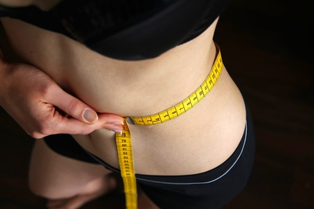 Woman with measuring tape measuring her hips Stock Photo