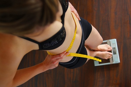 Woman with measuring tape on scales measuring her hips photo
