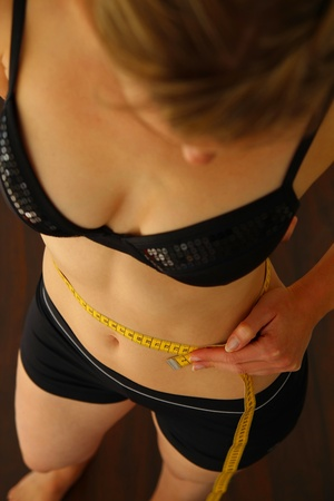 Woman with measuring tape measuring her hips photo