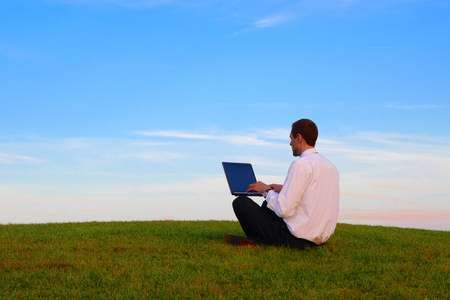 A Man with a Laptop siting on a green meadwo Stock Photo - 11870980