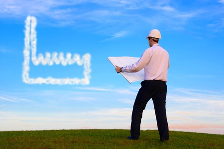 enterprising: Man with plan and cloud-factory standing on a meadow