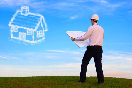 enterprising: Man with plan and cloud-house standing on a meadow