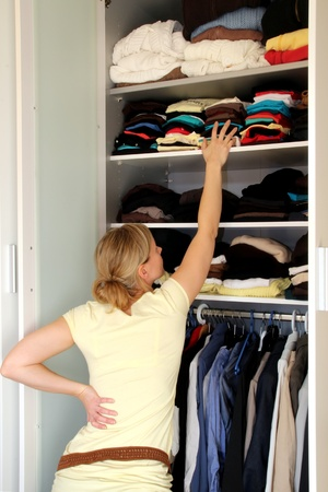 kitchen cabinet: Housewife in front of a filled wardrobe