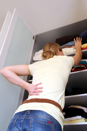 back kitchen: Housewife in front of a filled wardrobe