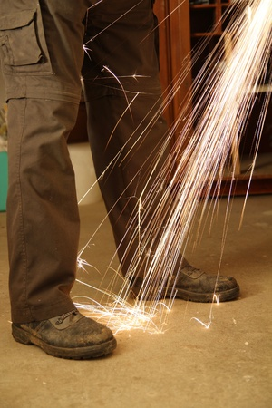 Worker with angle grinder only feets and sparks