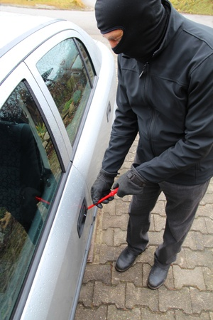 robo de autos: Robo de automóviles con un destornillador y una máscara y guantes Foto de archivo