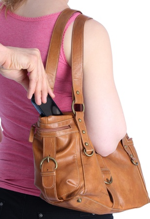 Pickpocketing a mobile out of a handbag of a woman photo