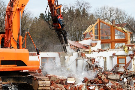 Demolition work on a house with an excavator Stock Photo