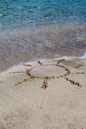 Sun painted in the sand with blue water in holiday Stock Photo - 12582595