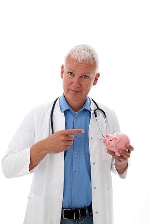 Senior Doctor pointiong an a piggy bank photo