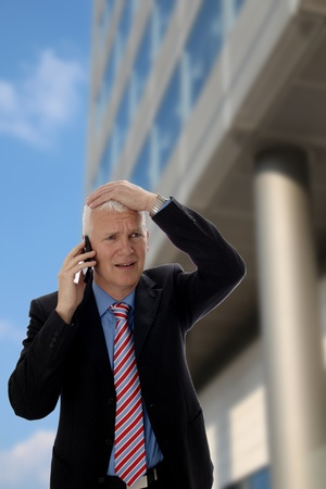cancellation: Senior Businessman disappointed in front of a Skyscraper Stock Photo