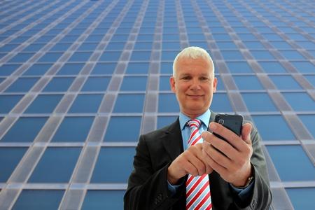 Senior Businessman writing on his mobile phone Stock Photo - 12867512
