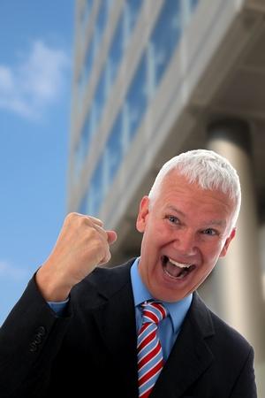 Senior Businessman crazy in front of a Skyscraper photo