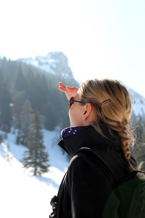 Woman looking up on a mountain in winter photo