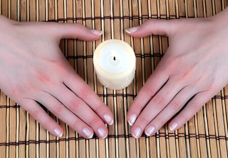 Hands in heart-shape covering a candle over bamboo mat photo