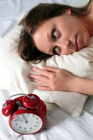 Young Woman awake with alarm clock photo