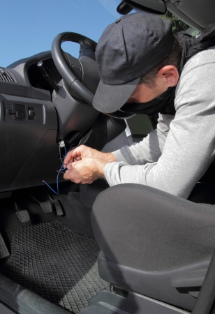 Car thief hot wiring the electrical circuits on the ignition of a car as he prepares to steal it