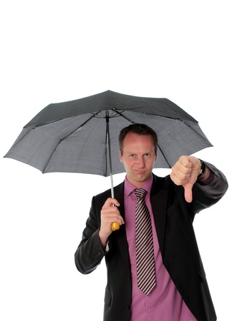 rueful: Businessman standing under an umbrella giving a thumbs down with a wry grimace as he indicates he is unsuccessful