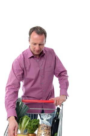 Mature man doing grocery shopping loading his purchases on to a trolley isolated on white