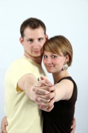 clasped: Young couple ballroom dancing with their arms extended and hands clasped with selective focus to their hands