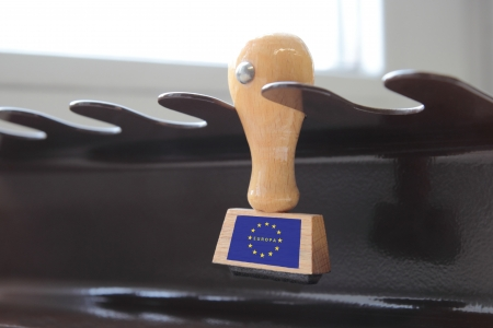 Hardwood office stamp with the emblem of the Eurozone hanging on a metal holder for stamping official documents and correspondence Stock Photo - 13806870