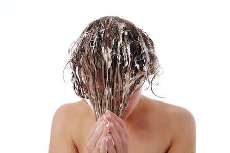 Woman with her wet soapy hair covering her face standing with bare shoulders washing and conditioning it
