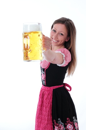 dirndl: Happy woman in dirndl smiling in welcome as she offers a glass filled with a large refreshing pint of beer