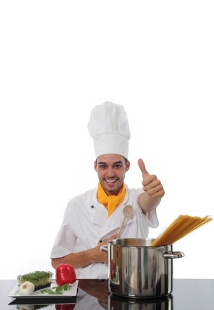 stainles steel: Chef in his toque giving a thumbs up of approval a he stands behind a stainless steel pot ready to cook spaghetti bolognaise