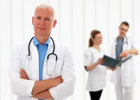 arms around: Senior doctor with his arms crossed and a stethoscope around his neck standing in front of his colleagues with shallow dof Stock Photo
