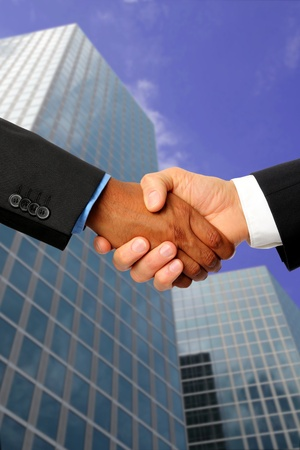 manos estrechadas: Apret�n de manos Internacional con edificio de oficinas en el fondo