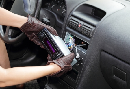 Gloved hands of a thief stealing a car radio from the dashboard of a car with the wiring exposed photo