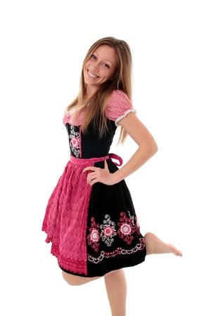 gestickt: Joyful Frau in der traditionellen bestickten rosa und schwarz Dirndl spielerisch aufwirbeln ihren nackten Fu�