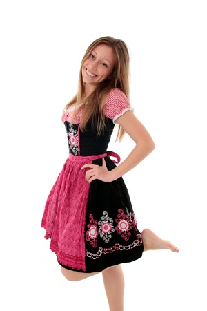 Joyful woman in traditional embroidered pink and black dirndl playfully kicking up her bare foot