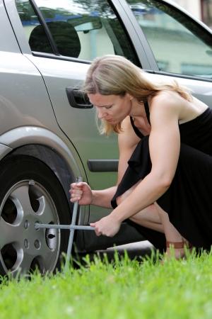mujer arrodillada: Mujer en un vestido de verano blck rodillas y cambiando un neumático de coche con una llave de ruedas Foto de archivo