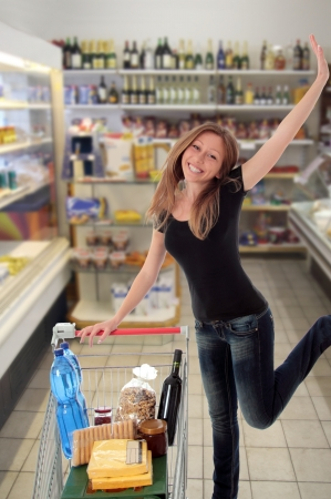 Happy woman with a trolley of groceries jumping for joy in the aisle of a supermarket photo