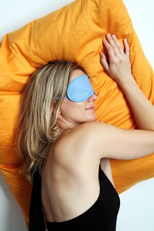 resting mask: Exhausted attractive blonde woman taking a mid day rest and sleeping on an orange cushion in a mask