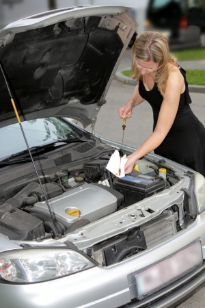 Woman driver with the bonnet of her car raised wiping the dipstick on a paper towel as she checks the engine oil level photo