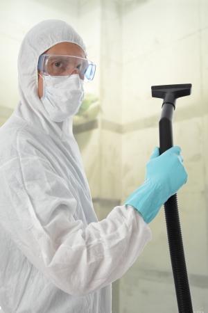 riesgo biologico: Limpiador profesional en el traje de protecci�n con gafas de seguridad y m�scara a punto de commense trabajo con su aspiradora para limpiar el interior de un edificio