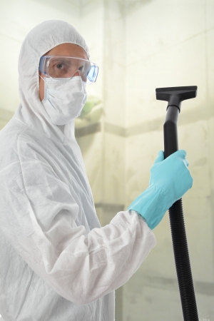 Professional cleaner in protective suit with safety goggles and mask about to commense work with his vacuum to clean the interior of a building photo