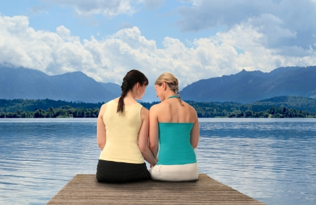 Two Women sitting on a boardwalk in front of a lake with mountain view photo