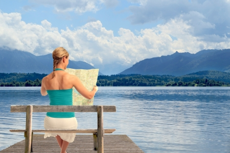 A young woman reading a map sitting on a bench in front of a lake photo